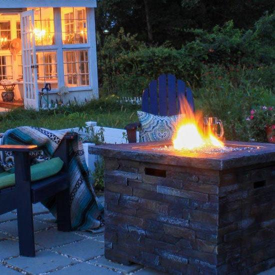 Cheminée au bio-ethanol cubique sur une terrasse en soirée.