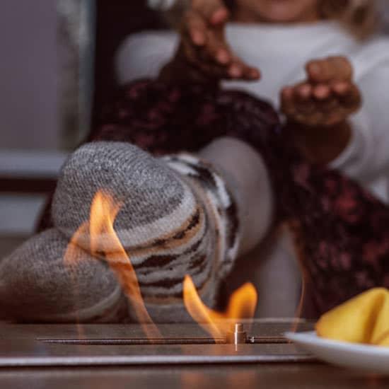 Une femme manifeste sa joie derrière la flamme d'une cheminée de table au bioéthanol